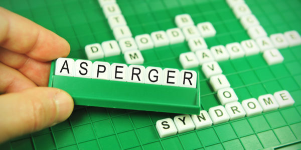 Hand showing the word Asperger (autism) on game board with keywords